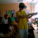 "JPVS dalyvis Ugnius išmegina ""Oculus Rift"" ir žaidimo metu rankomis naikina skaitmenines kliūtis."